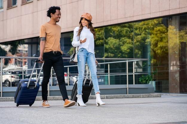 Ritratto di giovane coppia di turisti che trasportano valigia mentre si cammina all'aperto per strada. concetto di turismo.