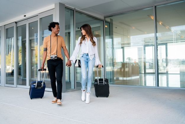 Ritratto di giovane coppia di turisti che trasportano la valigia mentre si cammina all'aperto sulla strada.