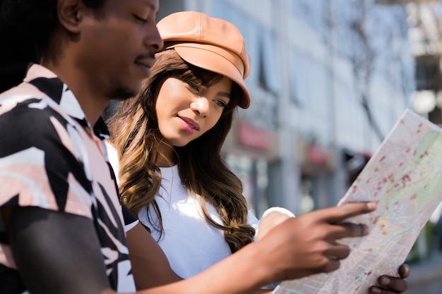 Ritratto di giovane coppia di turisti utilizzando la mappa e alla ricerca di direzioni mentre si cammina all'aperto