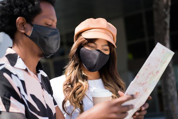 Ritratto di giovane coppia di turisti utilizzando la maschera protettiva e guardando la mappa mentre si cercano direzioni all'aperto