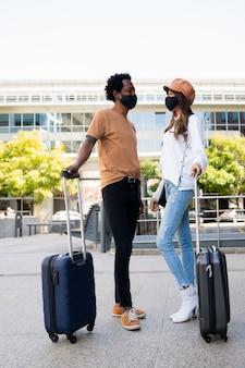 Ritratto di giovane coppia di turisti che indossa la maschera protettiva e che trasportano la valigia mentre in piedi fuori dall'aeroporto o dalla stazione ferroviaria concetto di turismo