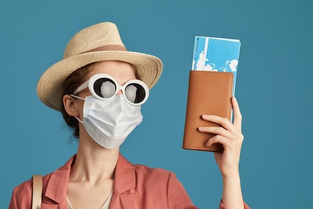 Ritratto di giovane turista in maschera protettiva in cappello e occhiali da sole isolati su priorità bassa blu