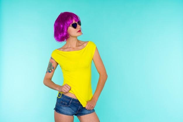Ritratto di giovane donna transgender con pelle problematica in parrucca rosa e occhiali da sole a forma di cuore su sfondo blu