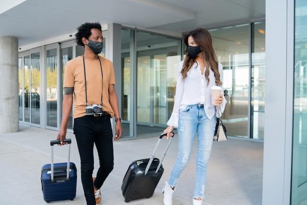 Ritratto di coppia giovane viaggiatore indossando maschera protettiva e portando la valigia mentre si cammina all'aperto sulla strada.