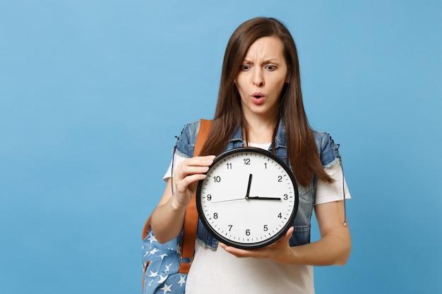 Ritratto di giovane studentessa perplessa sconvolta in vestiti di jeans con sveglia con zaino in mano isolata su sfondo blu. il tempo sta finendo. istruzione in università. copia spazio per la pubblicità.