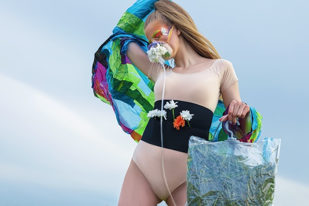 Ritratto di una giovane donna bianca con i capelli lunghi e trucco artistico creativo, con una maschera per l'ossigeno decorata con fiori, contro un cielo grigio, in un body e un impermeabile, tra le mani un pacchetto con l'erba