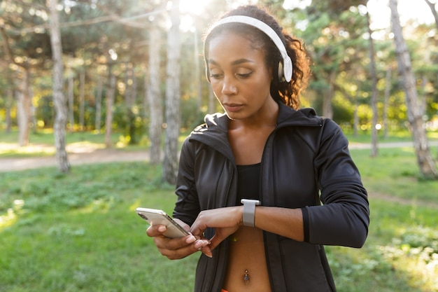 Ritratto di giovane donna 20s indossa tuta nera e cuffie, guardando l'orologio da polso mentre si cammina attraverso il parco verde