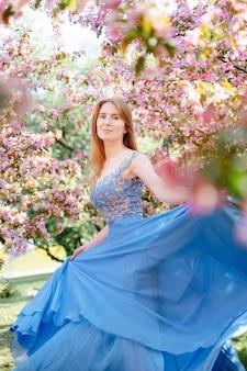 Ritratto di una giovane donna su uno sfondo di mele in fiore e ciliegi in primavera