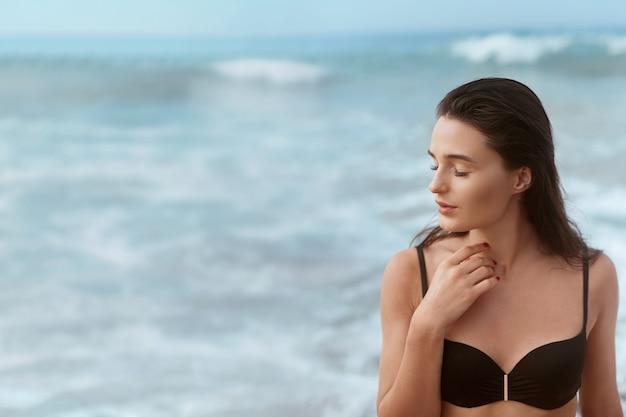 Ritratto di giovane donna in bikini nero sulla spiaggia tropicale che guarda l'obbiettivo. bella ragazza in costume da bagno