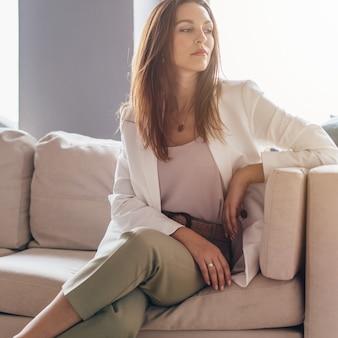 Ritratto di giovane donna in abbigliamento casual business seduto sul divano.