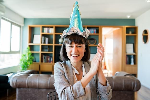Ritratto di giovane donna che celebra il compleanno in una videochiamata da casa.