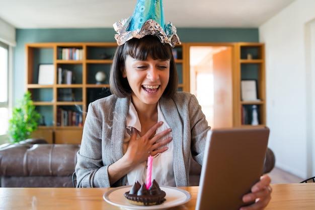 Ritratto di giovane donna che celebra il suo compleanno in una videochiamata con tavoletta digitale e una torta a casa