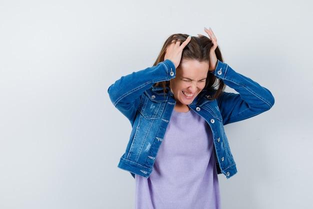 Ritratto di giovane donna che stringe la testa con le mani in maglietta, giacca e sembra irritata vista frontale