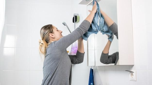 Ritratto di giovane donna che pulisce e lucida lo specchio in bagno mentre fa i lavori domestici.