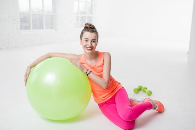 Ritratto di una giovane donna in abiti sportivi colorati sdraiata con una palla fitness sul pavimento nella palestra bianca