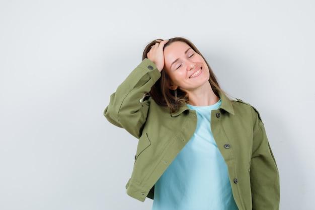 Ritratto di giovane donna che pettina i capelli indietro con la mano, chiudendo gli occhi in giacca verde e guardando gioviale vista frontale