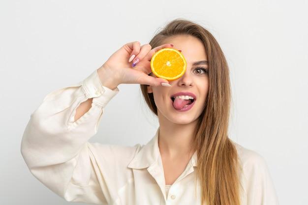 Ritratto di una giovane donna che copre gli occhi con una fetta d'arancia e sporge la lingua su sfondo bianco