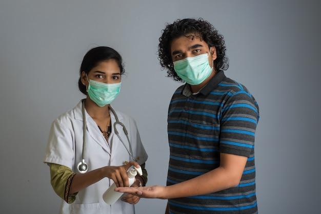 Ritratto di giovane donna medico e giovane utilizzando o mostrando un gel igienizzante da una bottiglia per la pulizia delle mani.