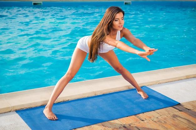 Ritratto di una giovane donna che fa esercizi di yoga sulla stuoia all'aperto al mattino