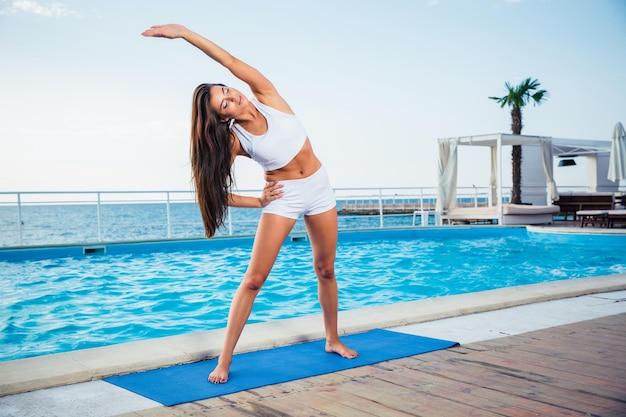 Ritratto di una giovane donna che fa esercizi di yoga all'aperto al mattino