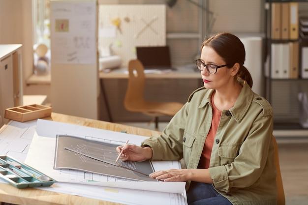 Ritratto di giovane donna disegno blueprint e piani mentre si lavora alla scrivania in ufficio ingegneri,