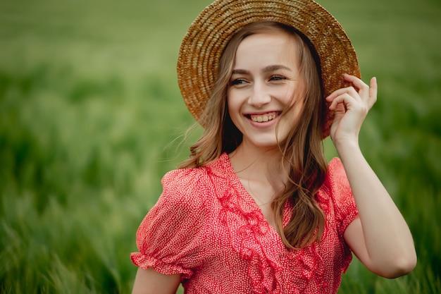 Ritratto di giovane donna in abito e cappello nel campo verde di orzo in campagna. ragazza alla moda nel momento pacifico godente rustico in erba di estate. momento rurale tranquillo