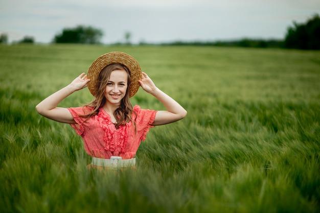 Ritratto di giovane donna in abito e cappello nel campo verde di orzo in campagna. ragazza alla moda nel momento pacifico godente rustico in erba di estate.