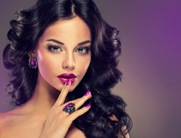 Ritratto di giovane donna vestita in uno splendido trucco da sera. acconciatura densa e ondulata perfetta. trucco, manicure e gioielli in tinte viola. arte dei capelli, cura dei capelli e trucco.