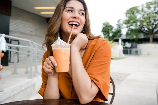Ritratto di giovane donna che beve un succo di frutta fresco in una caffetteria all'aperto