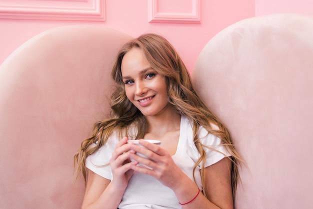 Ritratto di giovane donna che beve il tè e guardando con un sorriso fuori dalla caffetteria