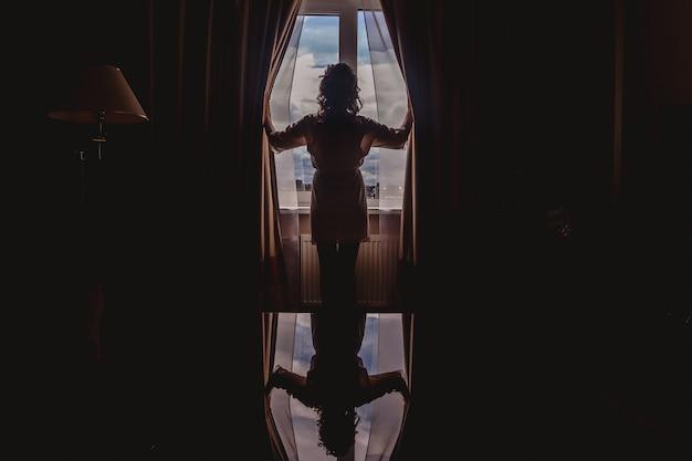 Ritratto di giovane donna in un elegante abito di seta in piedi alla finestra nella camera d'albergo. mattina di matrimonio. la sposa apre le tende nella stanza interna con riflesso nella luce di contorno. retrovisore. spazio del copyright
