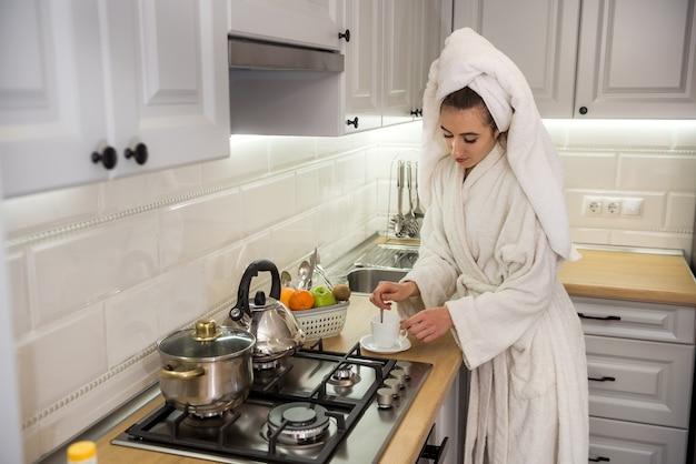 Il ritratto della giovane donna gode del caffè o del tè in cucina. mattina da sogno