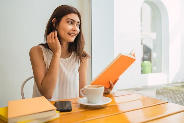 Ritratto di giovane donna che gode del tempo libero e legge un libro seduti all'aperto presso la caffetteria.