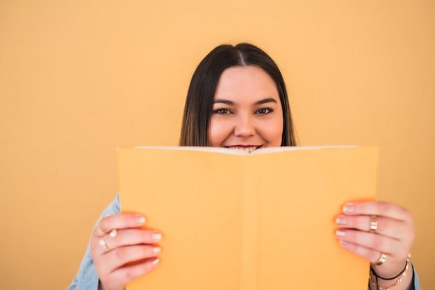 Ritratto di giovane donna che gode del tempo libero e legge un libro mentre levandosi in piedi contro il muro giallo