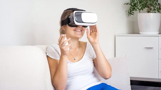 Ritratto di giovane donna che si diverte a usare gli occhiali vr e tiene in mano il telecomando.