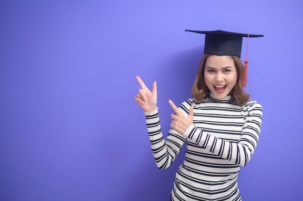 Un ritratto di giovane donna laureata su sfondo blu