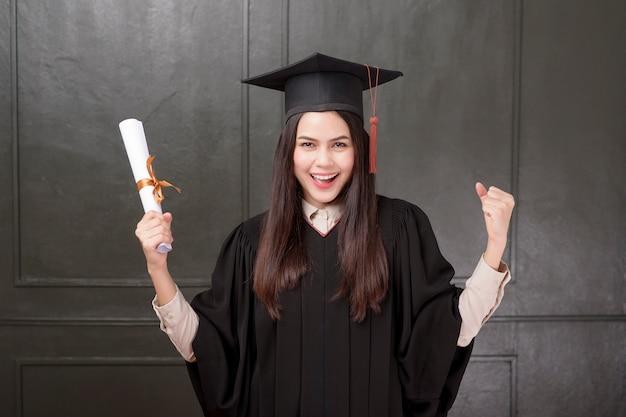 Ritratto di giovane donna in abito laurea sorridente e tifo su sfondo nero