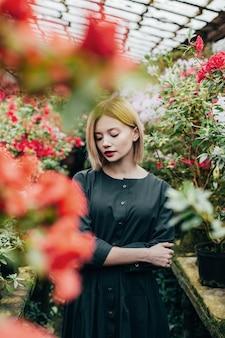 Ritratto di una giovane donna in un abito verde in una serra con azalee in fiore rosso e rosa
