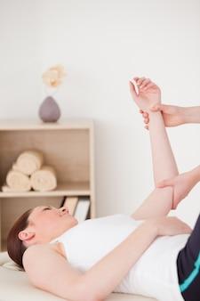 Ritratto di una giovane donna con un massaggio al braccio