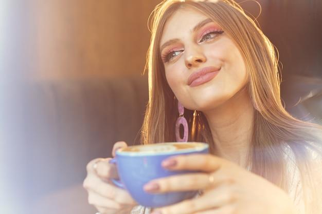 Ritratto di una giovane donna con una tazza di caffè e guardando attraverso la finestra
