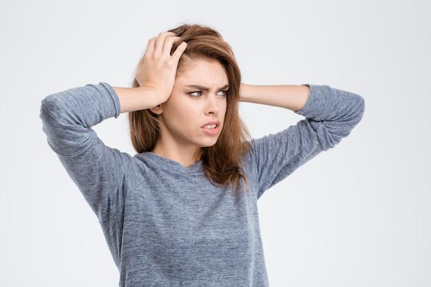 Ritratto di una giovane donna che ha mal di testa isolato su uno sfondo bianco