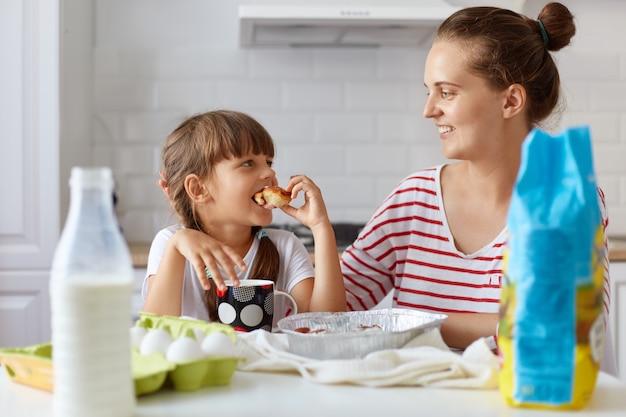 Ritratto di giovane donna e la sua piccola figlia carina seduti a tavola e mangiare torte e biscotti in cucina e bere bevande, divertirsi insieme mentre si gustano dolci appena sfornati.