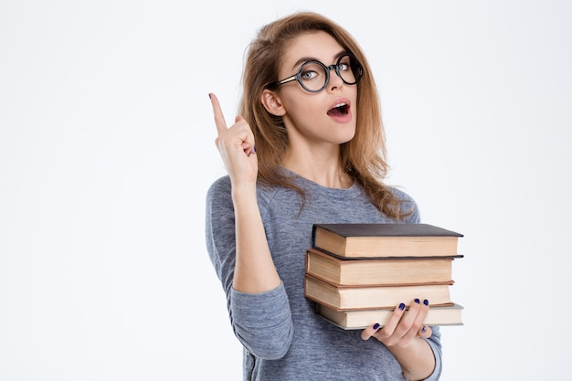 Ritratto di una giovane donna che tiene libri e punta il dito verso l'alto isolato su uno sfondo bianco