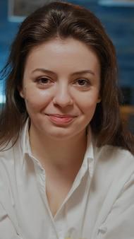Ritratto di giovane donna che tiene una ciotola di patatine seduto sul divano di casa. persona con ordine di cibo da asporto che guarda la telecamera sentendosi affamato, preparandosi a mangiare un pasto veloce