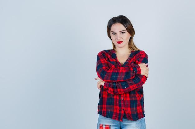 Ritratto di giovane donna che si abbraccia con una camicia a quadri e sembra una vista frontale sensata