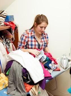 Ritratto di giovane donna che stira i vestiti nell'armadio