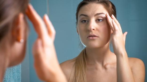 Ritratto di giovane donna in cerca di rughe intorno agli occhi mentre si guarda allo specchio.