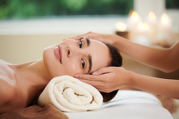 Ritratto di giovane donna che guarda l'obbiettivo mentre riceve un massaggio