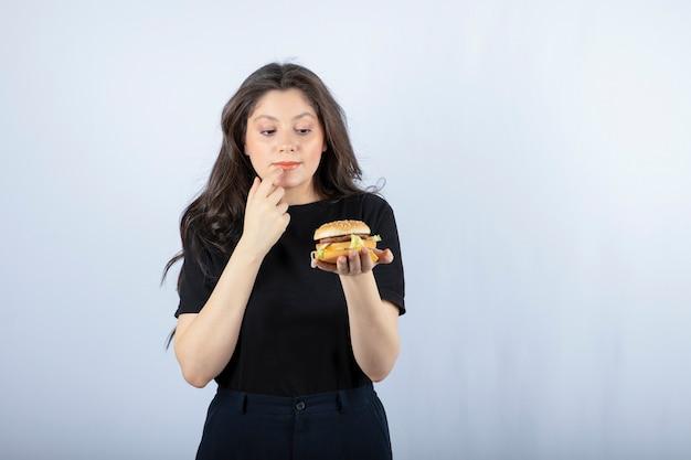 Ritratto di giovane donna che esamina delizioso hamburger sul muro bianco.