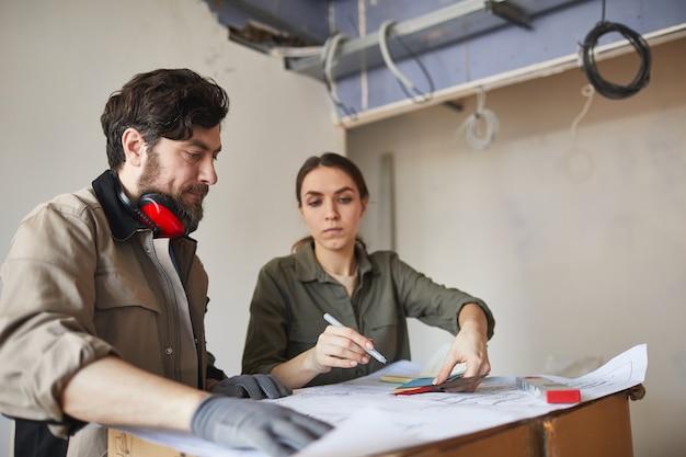 Ritratto di giovane donna che guarda le planimetrie con l'imprenditore edile mentre si discute di ristrutturazioni domestiche, copia dello spazio
